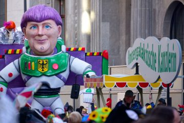 Cologne, Germany - March 3, 2014: Traditional carnival in Cologne, Germany. A large carnival float moves through the crowds in the streets while spectators cheer and shout for sweets.
