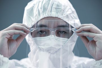 Closeup Asian male Doctor wearing face shield and PPE suit for Coronavirus outbreak or Covid-19, Concept of Covid-19 quarantine