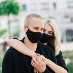 Couple wearing fashionable protective masks, walking in empty street of the city during quarantine.