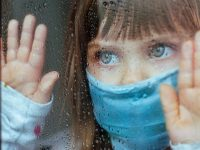 Little girl in face mask looking in the window glass with rain drops. Selective focus on the eyes. Social isolation stay at home during Pandemic COVID-19 concept.
