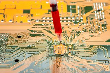 motherboard with contact paths of microcircuit and syringe with needle filled with red liquid, concept on topic of cospirology of vaccination and chipization of society given control to population.