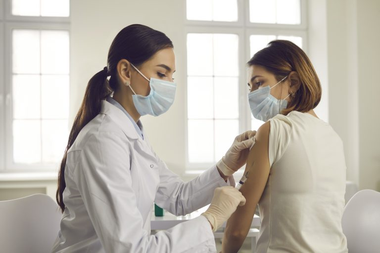 Professional doctor or nurse giving flu or COVID-19 injection to patient. Woman in medical face mask getting antiviral vaccine at hospital or health center during vaccination and immunization campaign