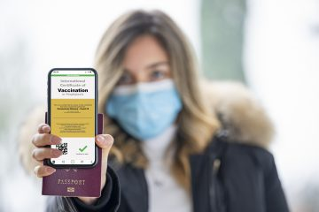 (Selective focus, focus on the smart phone) A defocused young girl, wearing a face mask, is holding a passport and a smart phone with a with an example of a certificate of vaccination against the Covid-19 disease.