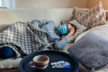 Sick woman having flu or cold. Girl lying in bed having headache wearing protective mask by pills and water on table.