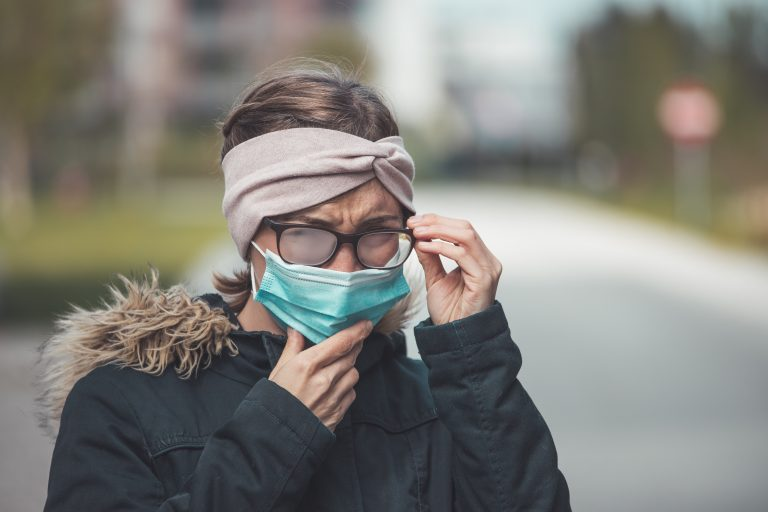 Young woman outdoors wearing a face mask and glasses, tarnished glasses