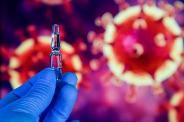 Coronavirus vaccine. A hand in medical gloves holds a vaccine and a syringe against the background of the image of a coronavirus. covid-19,