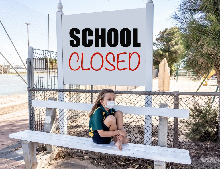 Covid-19 outbreak schools closures. Sad and bored Schoolgirl kid with face mask feeling depressed and lonely outside her closed school. Restrictions and lockdown as Coronavirus containment measures.
