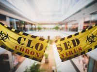 End of coronavirus COVID-19 economic lockdown. Cutting and tearing caution tape at shopping mall. Easing restrictions