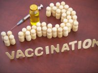 People (wooden figures) shaped as question mark, vaccine bottle, syringe and word vaccination. Questions about vaccination concept.