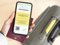 (Selective focus) Overhead view of an human hand holding a passport and a smart phone with a digital illustration of an example of a certificate of vaccination against the Covid-19 disease.