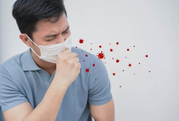 close up asian man coughing inside face mask with coronavirus and droplets icon for COVID-19 preventive concept