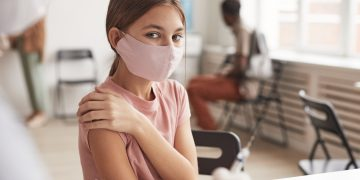 Portrait of cute girl wearing pink mask and looking at camera while waiting for vaccination in clinic, copy space