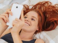 Portrait of young cheerful red-haired woman using smartphone while lying in bed